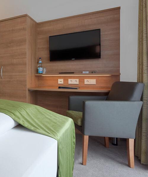 Hotelzimmereinrichtung mit bequemen Sessel und zahlreichen integrierten Steckdosen