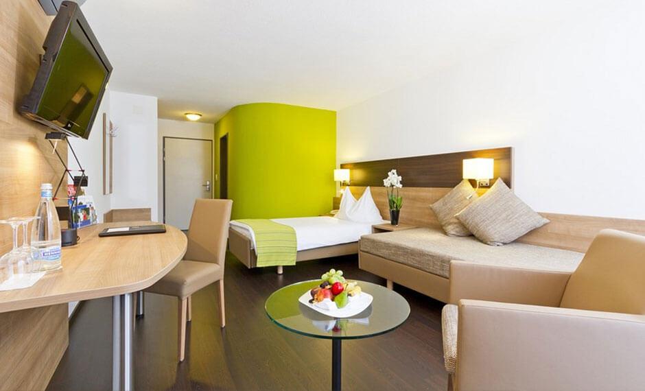 Hotelzimmereinrichtung City Comfort mit hellgrünen Umbauten