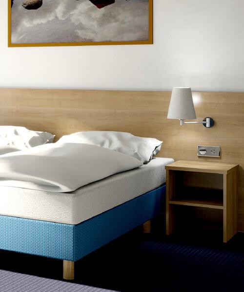 Hotelzimmer in Holzmaserung mit blauem Akzent als Bettrahmen