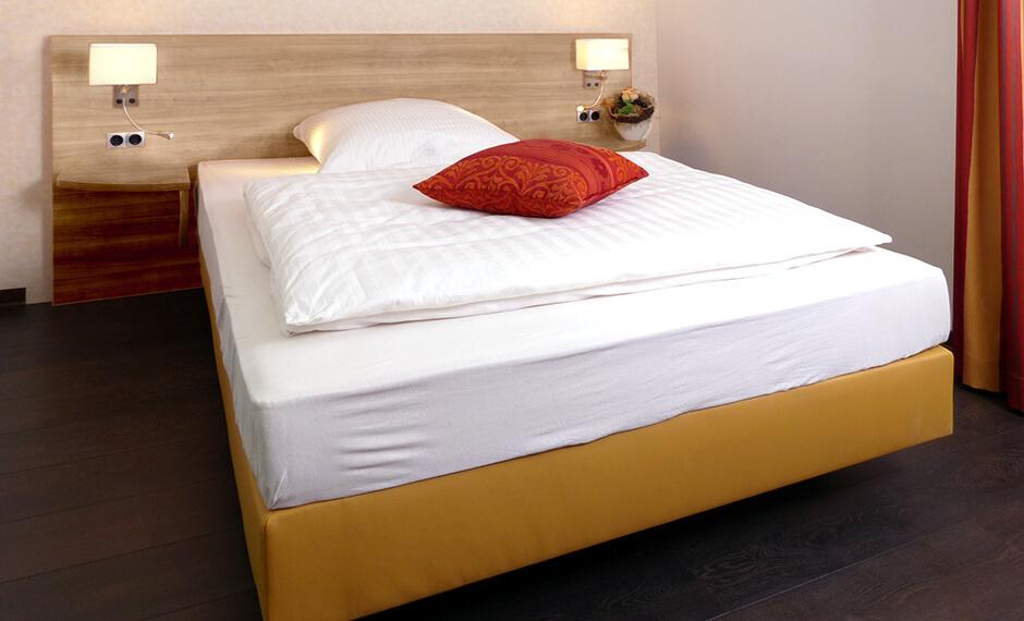 Hotelzimmereinrichtung - ein einfach gemütliches Hotelbett mti rotem Kissen