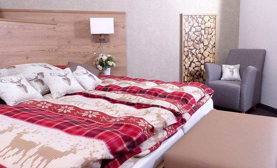 Wandpaneele, Bett und ausgefallenes Lampendesign als Hotelzimmereinrichtung
