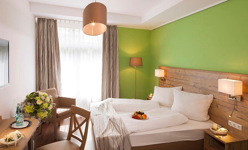 Peppiges Grün kombiniert mit Holz in der Hotelzimmereinrichtung