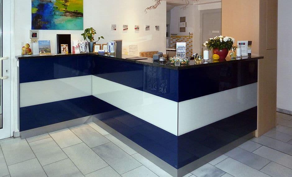Moderne Rezeptionstheke in Blau-Weiß passend zur Lobby-Einrichtung